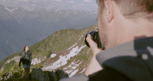 A Woman Having Her Photo Taken On The Mountain Top