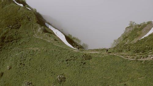 A Couple Hiking A Mountain Trail