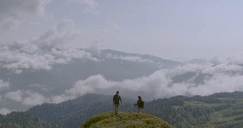 A Couple Reaching The Mountain Summit