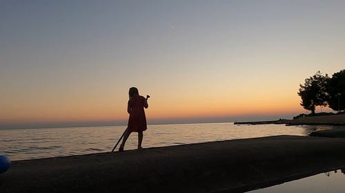 Little Girl Playing With A Paddle Near The Shore