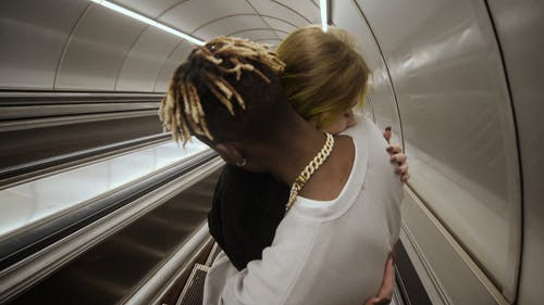 A Couple Hugging In The Subway Escalator