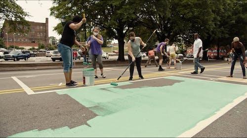 Volunteers Painting The Street With Mural