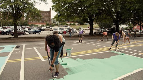 Group Of People Painting Mural In The Street