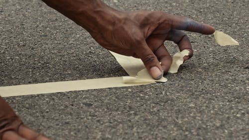 Taping A Marker On The Concrete Road