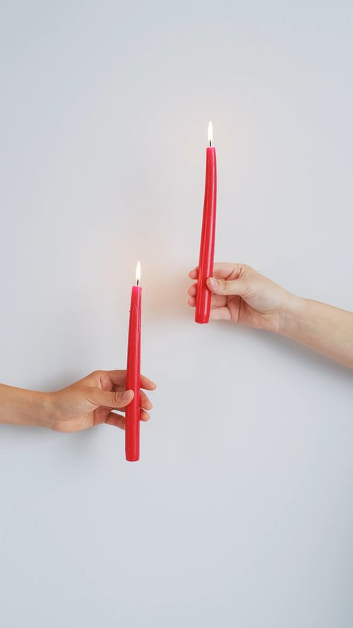 Hands Holding Red Candles