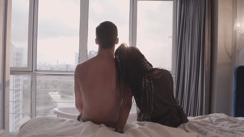 A Couple Sitting On The Bed Looking At The City View By The Window