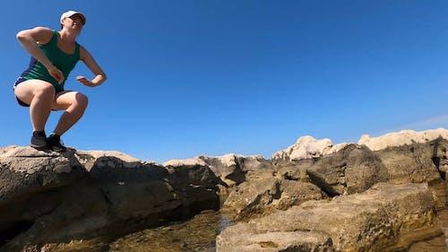 Woman Walking On Rocks On The Sea