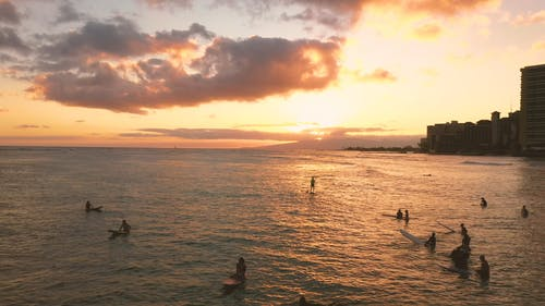 Surfers On The Beach In Hawaii At Sunset
