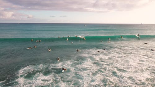 Surfers Riding The Big Waves Of The Sea