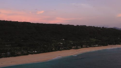 Aerial Shot Of A Beach Shoreline At Sunset