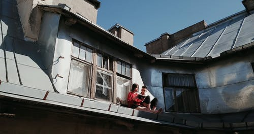 Couple Reading a Book While Sitting on Roof