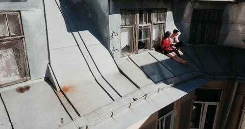 Drone of Footage Couple Sitting While Talking on Roof
