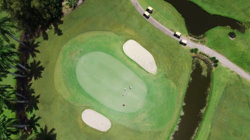 Golfers Playing On The Green Of A Golf Course