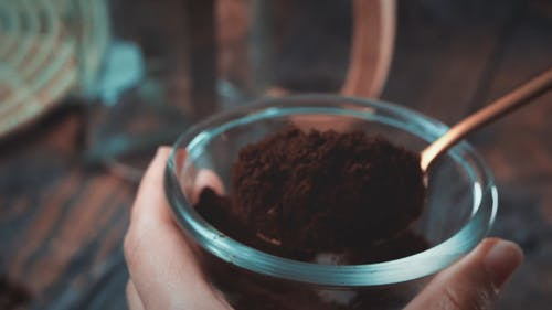 Close-Up View of Person Scooping Black Coffee Powder