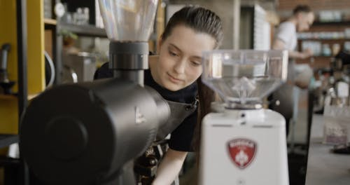 A Female Barista Smelling The Fresh Grind Coffee Beans
