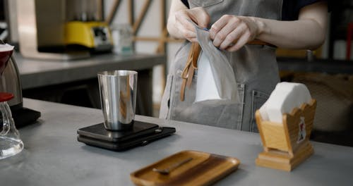 Pouring And Weighing Fresh Coffee Bean Over A Tin Cup