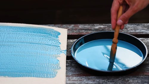 Person Mixing A Blue Paint