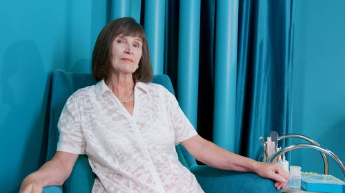 Woman Sitting on Blue Chair While Looking Serious