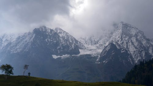 Snow Covered Mountains Under Cloudy Sky