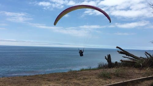 Person Paragliding Under Blue Sky and White Clouds