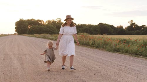 Mom and Daughter Running on Dirt Road While Holding Hands
