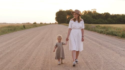 Woman Walking on Dirt Road While Holding Hands With Her Child