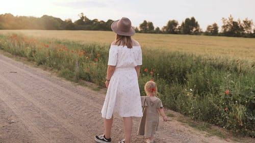 Mom and Daughter Walking on Dirt Road