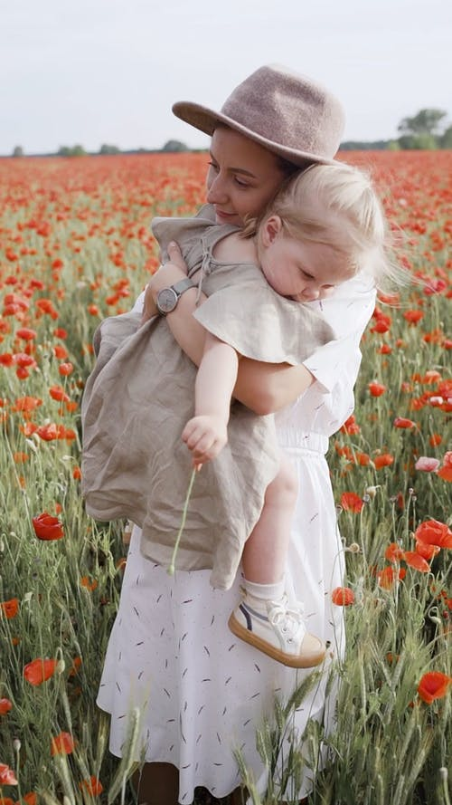 Woman Carrying Her Baby While Standing on Red Poppy Flower Field