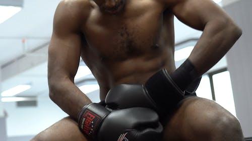 Man Putting on Boxing Gloves