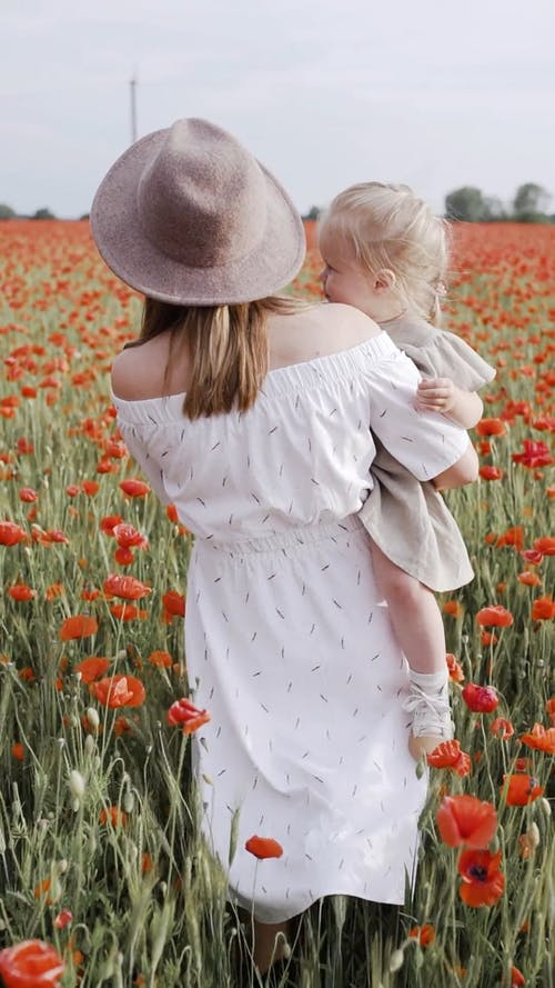 Woman Walking on Red Poppy Flower Field While Carrying Her Child
