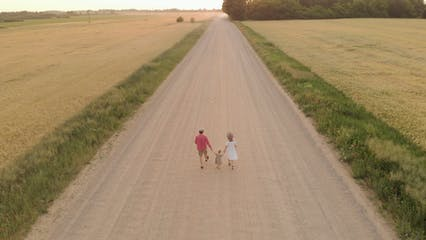 Drone Footage Of Family Walking On Dirt Road