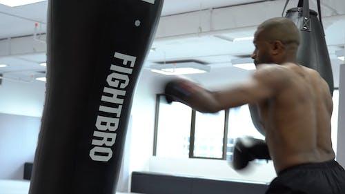 A man Hitting The Heavy Bag Inside A Gym
