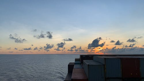 Cargo Ship In The Open Sea At Sunset