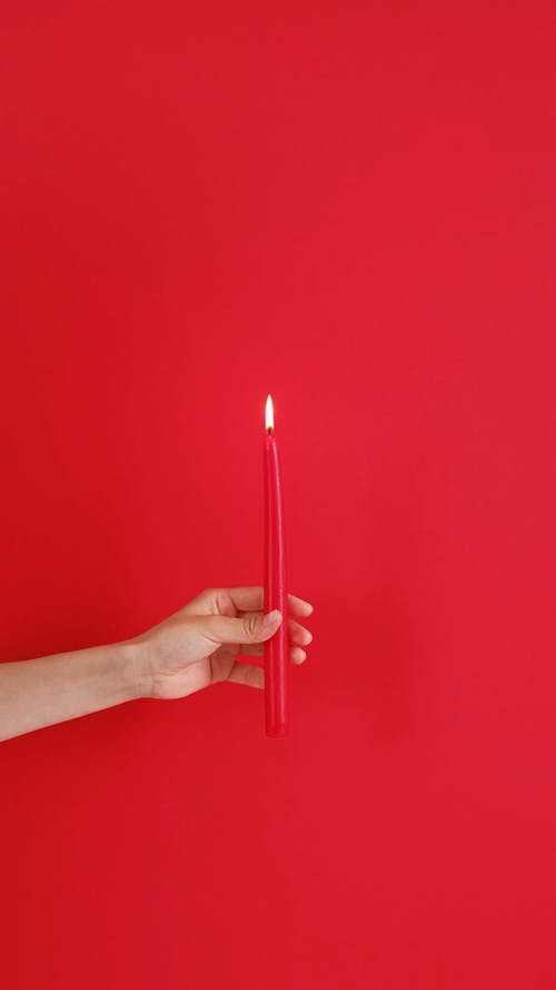 Hand Holding a Red Candle
