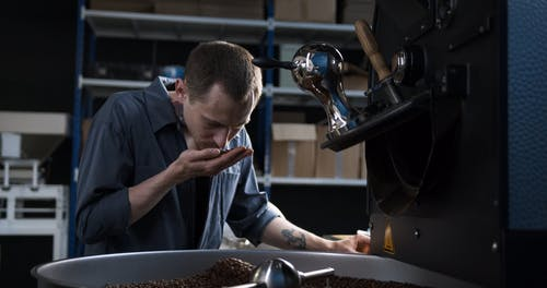 A Man Smelling The Aroma Of Coffee Beans