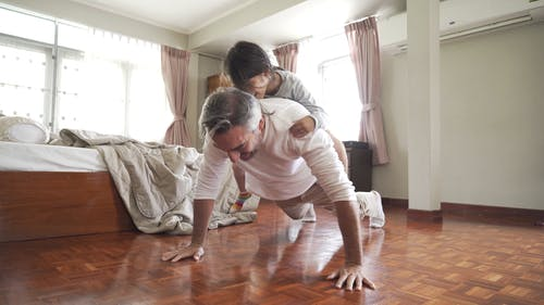 Dad Doing Push-Ups While Carrying His Child on His Back