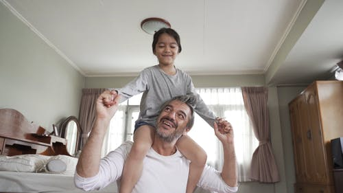 Father Carrying His Child on His Back While Having Fun