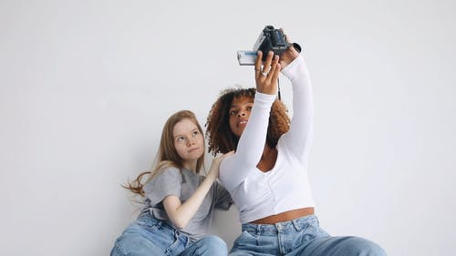 Two Women Smiling While Looking at Video Recorder