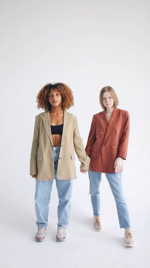 Two Women Looking Serious While Holding Hands