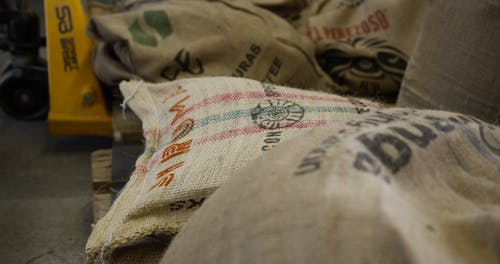 A Male Worker Bringing In The Sacks Of Coffee Beans