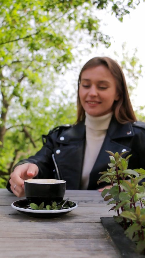 A Woman Dinking A Cup Of Coffee Outdoor
