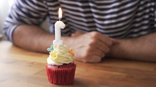 Person Blowing the Candle in the Cake