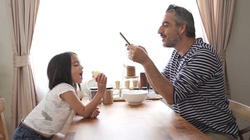 A Father Taking Photo Of Her Daughter Eating A Cupcake