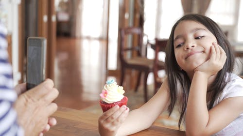 Dad Taking Picture Of Her Daughter Holding a Cupcake