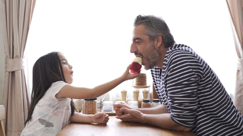 A Father And Daughter Sharing  A Cupcake