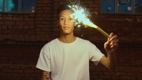 A Young Man Holding A Fireworks Sparkle