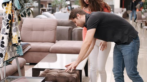 A Couple Checking Out The Cushion Of A Chair In A Furniture Shop