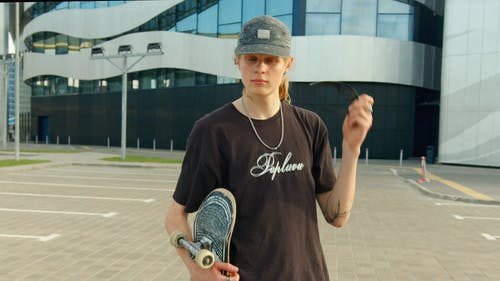 A Young Skateboarder Putting On His Sunglasses