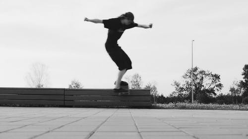Two Young Men Doing A Boardslide Over A Railing