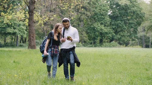 Man and Woman Looking at Smartphone While Walking on Grass Field